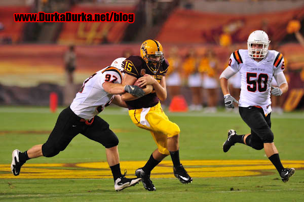 ASU QB Danny Sullivan is tackled by ISU DL Rustin Phillips after a run up field.