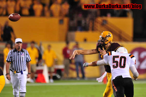 ASU QB throws before being tackled by ISU DL Sean Rutten.