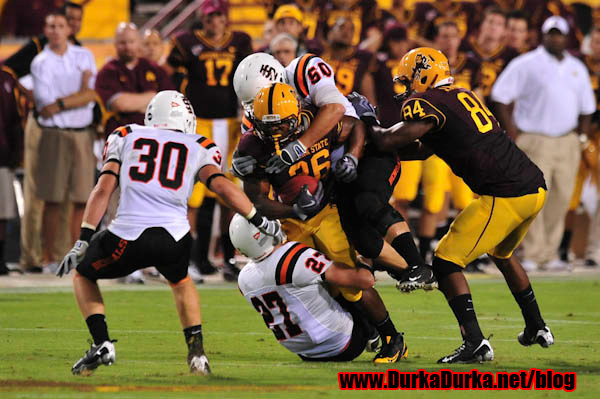ASU RB Shaun DeWitty is tackled by ISU DL Sean Rutten (50) and DB Dustin Tew (27)