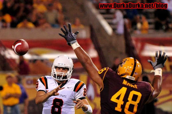 ISU QB Kyle Blum throws while ASU LB Brandom Magee tries to block the pass.