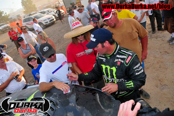 Robby Gordon signs autographs for fans at the finish.