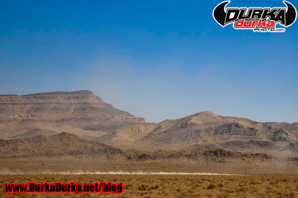 An unknown drivers racers across the desert.