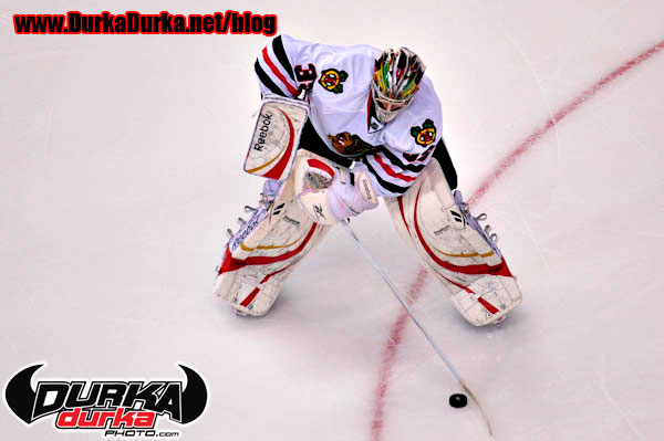Blackhawks goaltender Cristobal Huet comes out of the net to clear the puck.